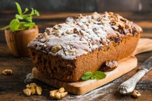 Sweet fruitcake with walnuts, dates and icing sugar on the wooden rustic table