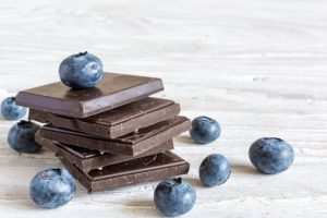 Dark chocolate stack with fresh ripe blueberries on white wooden table. close up